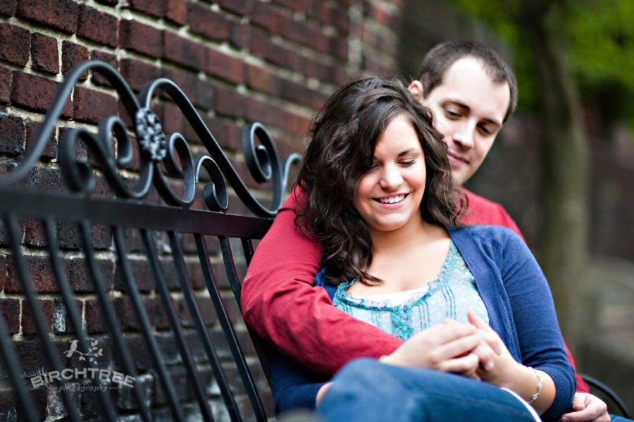couple sitting on bench in mellon park for engagement session in pittsburgh