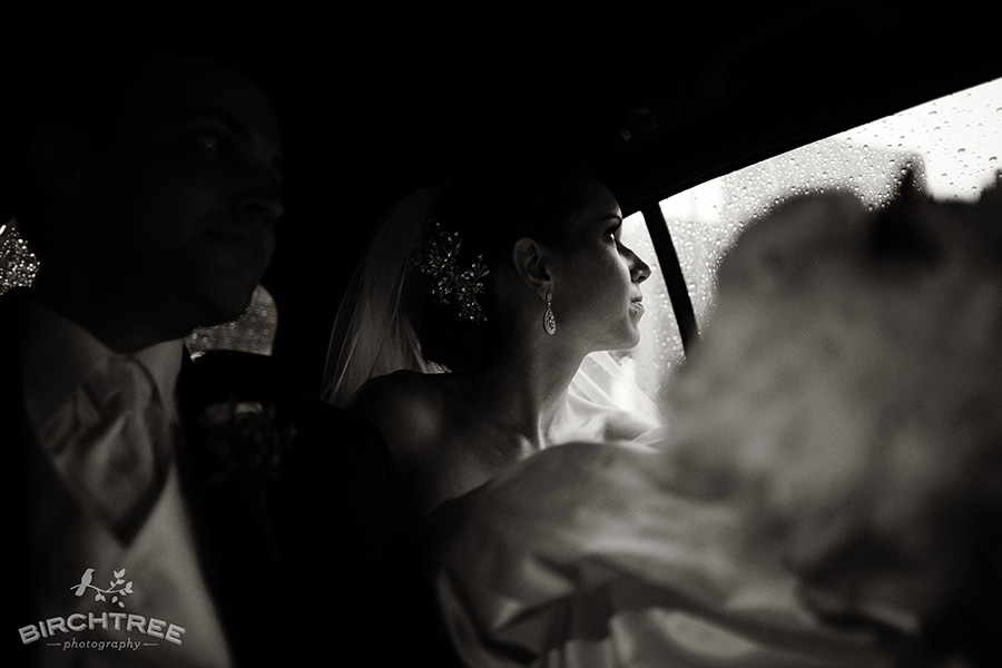 bride stares out car windo on rainy ride to reception